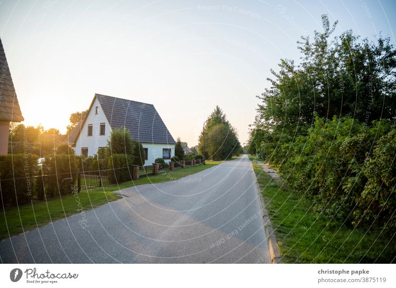 Haus in ländlicher Umgebung Einfamilienhaus Immobilie Eigenheim wohnen Weg Sonnenuntergang Sonnenlicht Menschenleer Häusliches Leben wohnen im grünen Gebäude