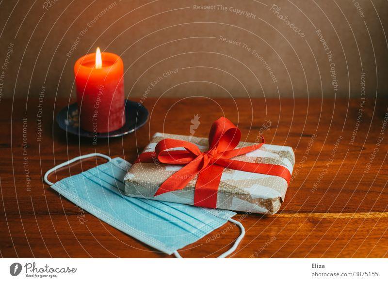 Geschenk mit Kerze und Mundschutz . Weihnachten und Advent während der Corona Pandemie. Weihnachtsgeschenk besinnlich Maske Mundnasenschutz Coronavirus