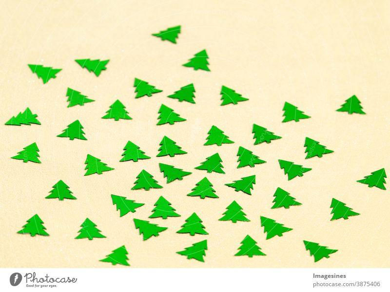 Moderne Weihnachtskomposition. grüne Weihnachtsbäume Konfetti auf gelbem cremefarbenem Hintergrund. Streudeko Dekoration Weihnachten abstrakt Kunst Herbst