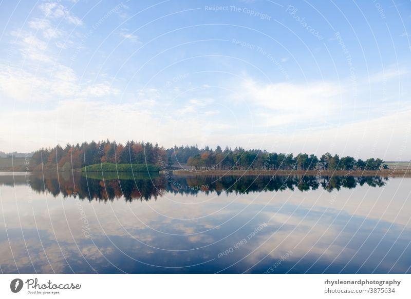 Atemberaubend blauer Himmel reflektiert im Spiegel wie das Wasser des Redmires-Reservoirs Wald Nadelbäume Herbst Textur Landschaft Reflexion & Spiegelung Bäume