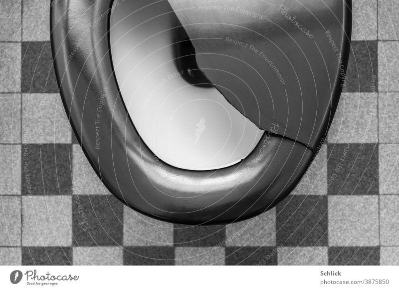 BRECHDURCHFALL Toilette WC in Vogelperspektive mit zerbrochenem schwarzem Deckel und Fußboden aus alten Keramikfliesen Klodeckel Klobrille vintage