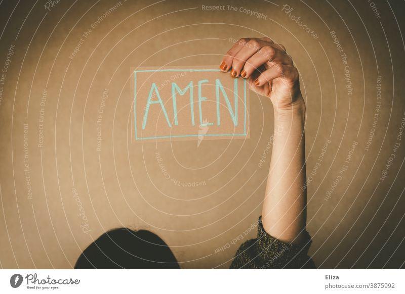 Eine Frau hält ein Schild auf dem Amen steht. Konzept beten, predigen und Kirche. Beten Glaube Gebet Predigt heilig Religion Gottesdienst Amen sagen
