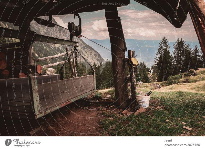 Lastenseilbahn auf der Alm - Ausblick ins Tal der Alpen - Holzunterstand als Schutz vor dem Wetter - der Materialträger für die Versorgung des Bauernhofes im Gebirge ist aus Holz gefertigt