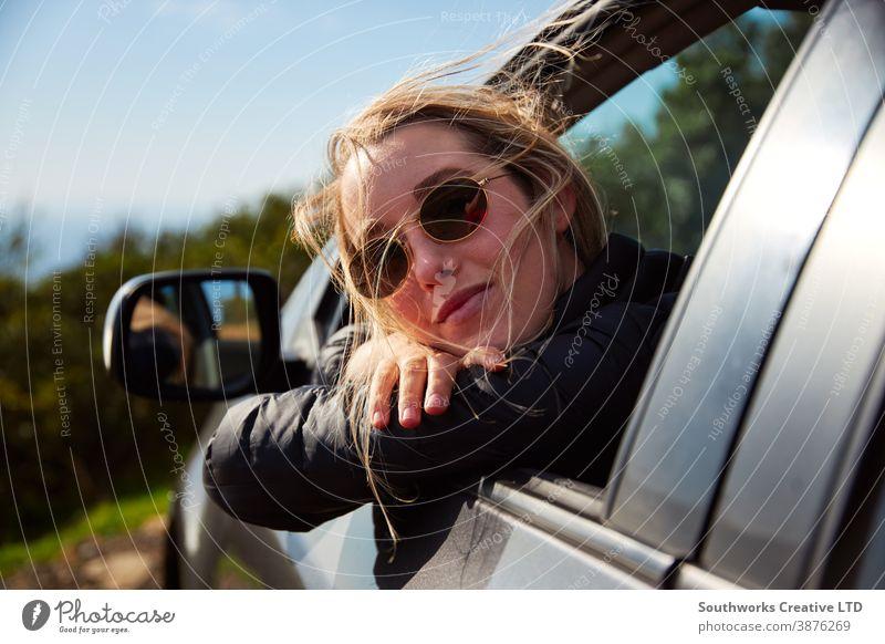 Junge Frau auf Roadtrip-Urlaub aus dem Mietwagenfenster gelehnt mit Berglandschaft im Rücken Autoreise Autovermietung Feiertag Junge Frauen PKW fahren Fahrer