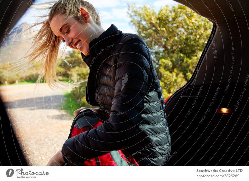Frau in offener Heckklappe des Autos legt Thermoskanne in Rucksack, bereit für Wanderung auf dem Land laufen wandern Junge Frauen Spaziergang aktiv Verpackung