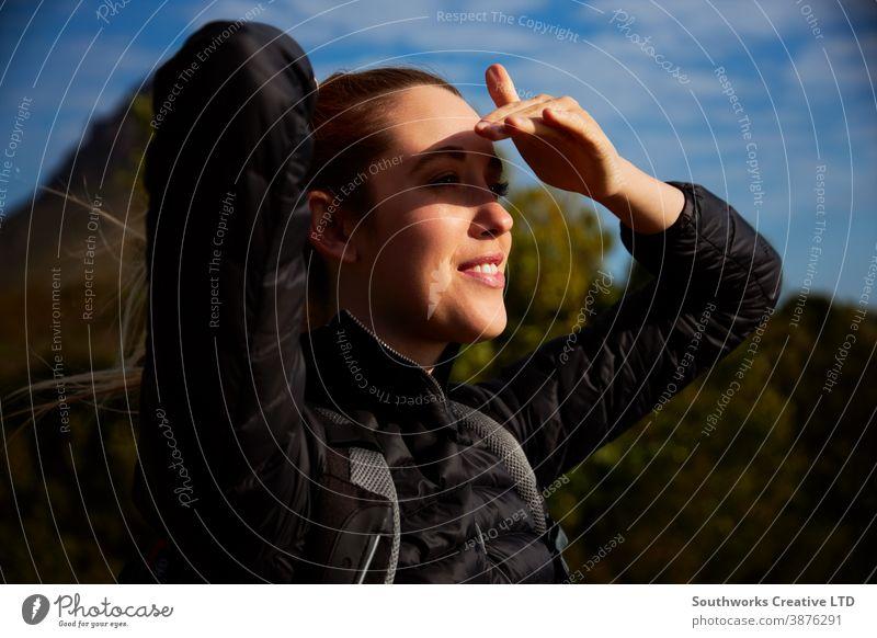 Aktive junge Frau wandert auf dem Land und schirmt ihre Augen vor der Sonne ab staycation Reisen Junge Frauen Wanderung wandern Spaziergang laufen aktiv