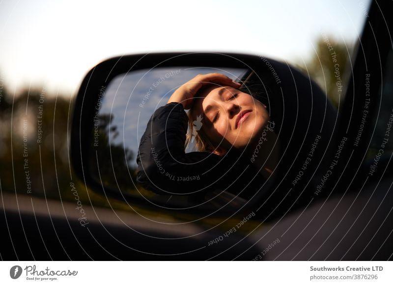 Reflexion im Fahrspiegel einer jungen Frau auf Autoreise Urlaub, die sich aus dem Fenster eines Mietwagens lehnt PKW Autovermietung Junge Frauen Feiertag fahren