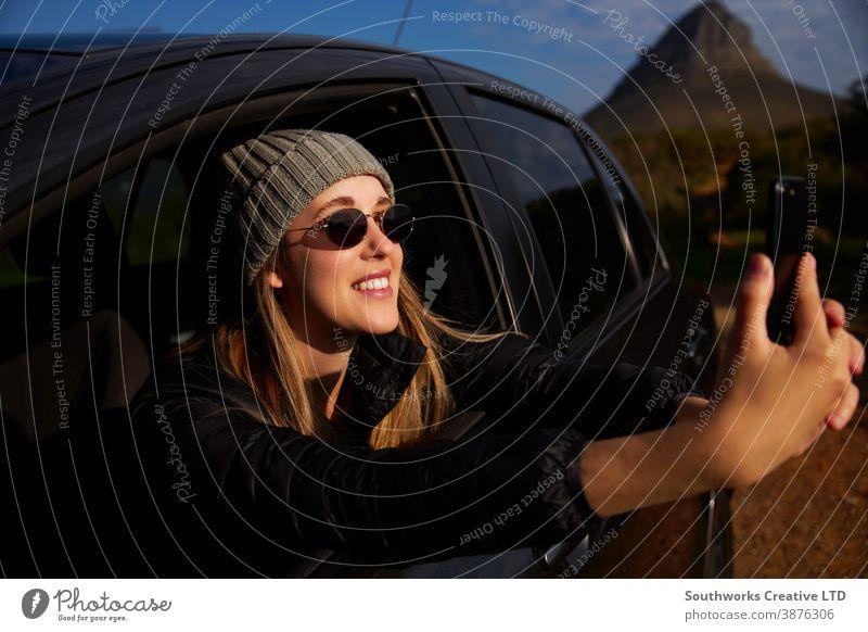 Junge Frau auf Autoreise Urlaub Fotografieren aus dem Fenster eines Mietwagens am Mobiltelefon Junge Frauen Feiertag PKW fahren Fahrer Autovermietung Reisen