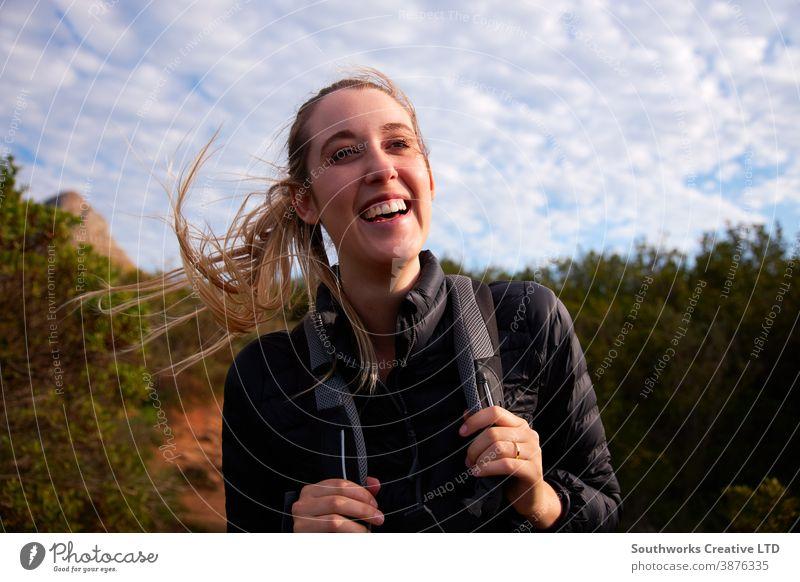 Porträt einer jungen Frau mit Rucksack beim Wandern auf einem Pfad durch die Landschaft Lächeln Junge Frauen Wanderung wandern Spaziergang laufen aktiv Feiertag