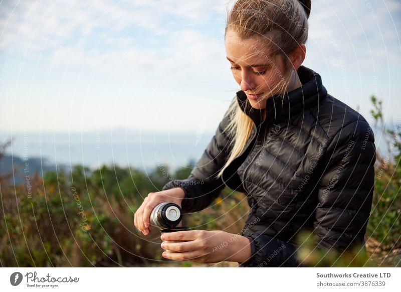 Junge Frau macht eine Pause vom Wandern auf dem Land und gießt Kaffee aus der Flasche Wanderung laufen Junge Frauen wandern Spaziergang Camping
