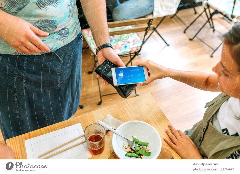 Weiblicher Kunde, der die Restaurantrechnung mit einer virtuellen Handykarte bezahlt bezahlen Kreditkarte Geld sicherer Handel Draufsicht elektronisch Zahlung