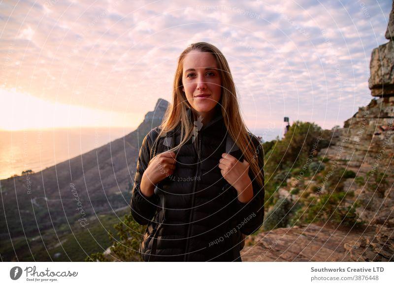 Porträt einer jungen Frau, die entlang des Küstenweges wandert, während die Sonne hinter ihr über dem Meer untergeht Junge Frauen Wanderung wandern Spaziergang