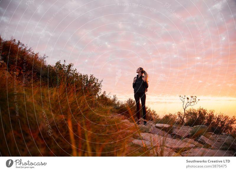 Frontansicht einer jungen Frau mit Rucksack, die bei Sonnenuntergang zu einer Wanderung auf dem Landweg aufbricht Abenteuer Sonnenaufgang Junge Frauen wandern