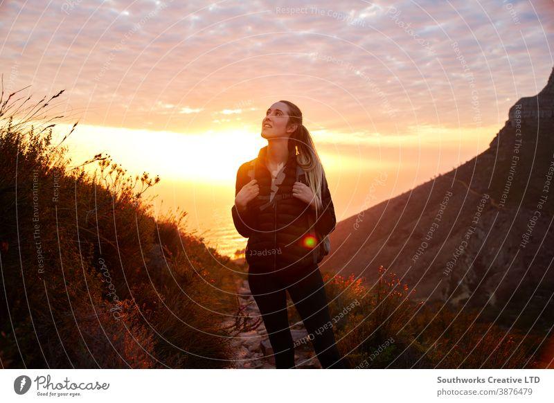 Frontansicht einer jungen Frau mit Rucksack, die bei Sonnenuntergang zu einer Wanderung entlang des Küstenweges aufbricht Abenteuer Sonnenaufgang goldene Stunde