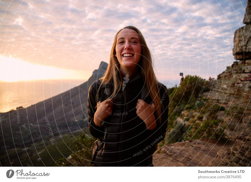 Porträt einer lächelnden jungen Frau, die entlang des Küstenweges wandert, während hinter ihr die Sonne über dem Meer untergeht reisen Urlaub Glück Junge Frauen
