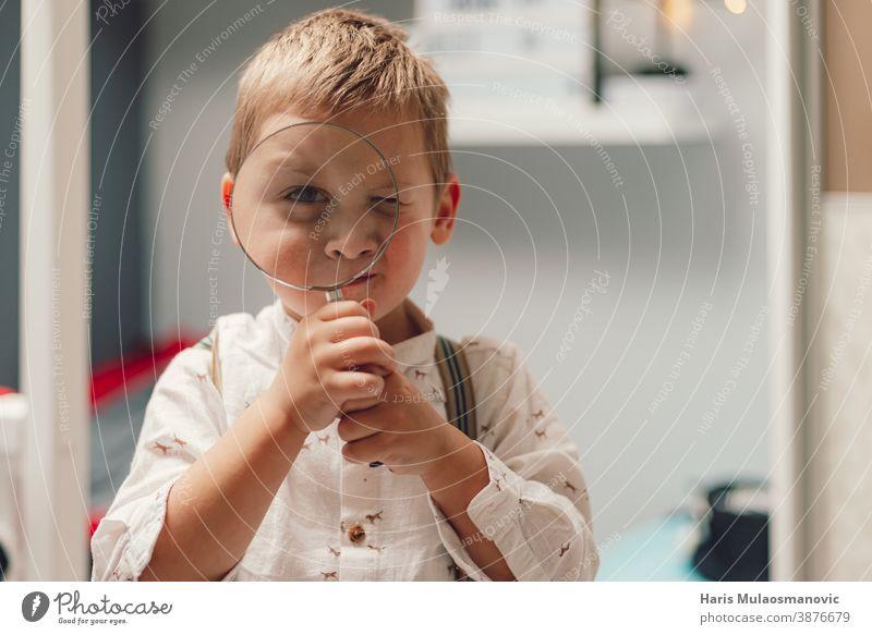 Süßer kleiner Junge mit einer Lupe in der Hand schön Pflege Kaukasier Kind Kindheit Konzept Neugier neugierig neugieriger Junge niedlich Bildung Gesicht finden