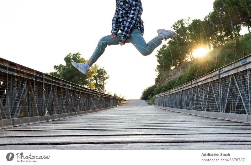 Energetische Hipster Mann springt über Holzbrücke springen hoch Brücke Energie Spaß haben Sprung aktiv Fliege männlich Steg Weg Fußweg Freiheit genießen