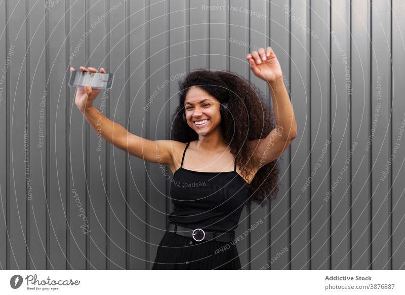Glückliche ethnische Frau tanzt auf der Straße Tanzen Musik zuhören Kopfhörer fröhlich Spaß haben genießen sich[Akk] bewegen schwarz Afroamerikaner Freude Klang