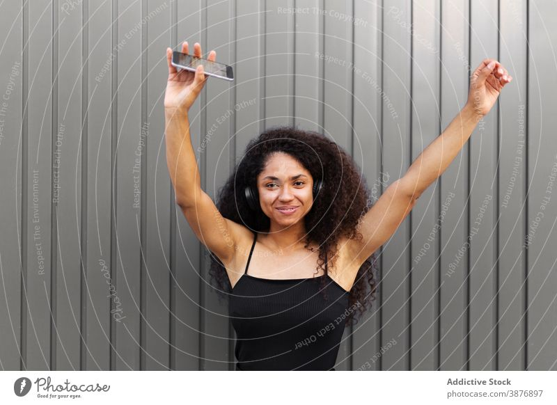 Optimistische schwarze Frau, die auf der Straße Musik hört zuhören Kopfhörer meloman genießen Afro-Look Frisur krause Haare Smartphone ethnisch Afroamerikaner