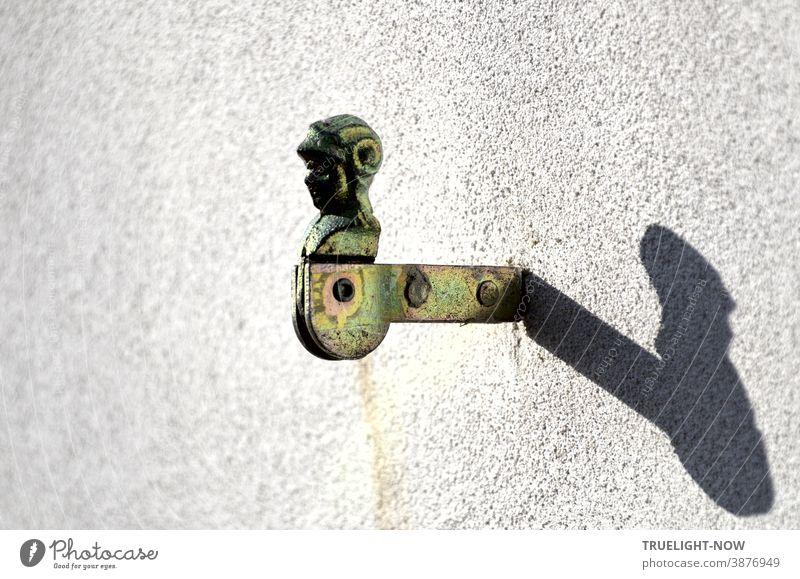 Verzinkter Fensterladenhalter  in Form eines Ritterkopfes oder Sturmhaubenträgers mit Drehgelenk und zwei Nieten im Träger ist in eine weisse Hauswand eingemauert und wirft im Sonnenlicht einen starken Schatten