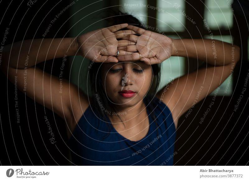 Eine junge und attraktive indisch-bengalische brünette Frau in aktiver Kleidung macht Yoga, nachdem sie morgens vor dem Fenster in ihrem Zimmer aufgewacht ist. Indischer Lebensstil.