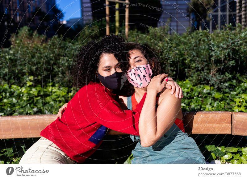 Lesbisches Paar mit Sonnenbrille, das sich auf einer Parkbank umarmt und entspannt Frau lesbisch Bonden Person Homosexualität Liebe Lifestyle Umarmung