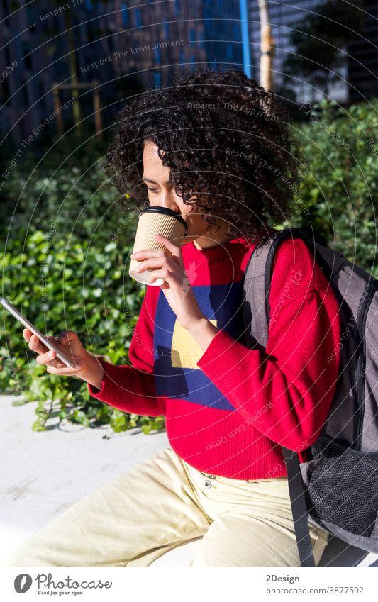 Hübsche junge Afro-Frau sitzt auf einer Bank im Freien, benutzt ihr Mobiltelefon und trinkt eine Kaffeetasse zum Mitnehmen Sitzen Mobile Smartphone Mitnahme