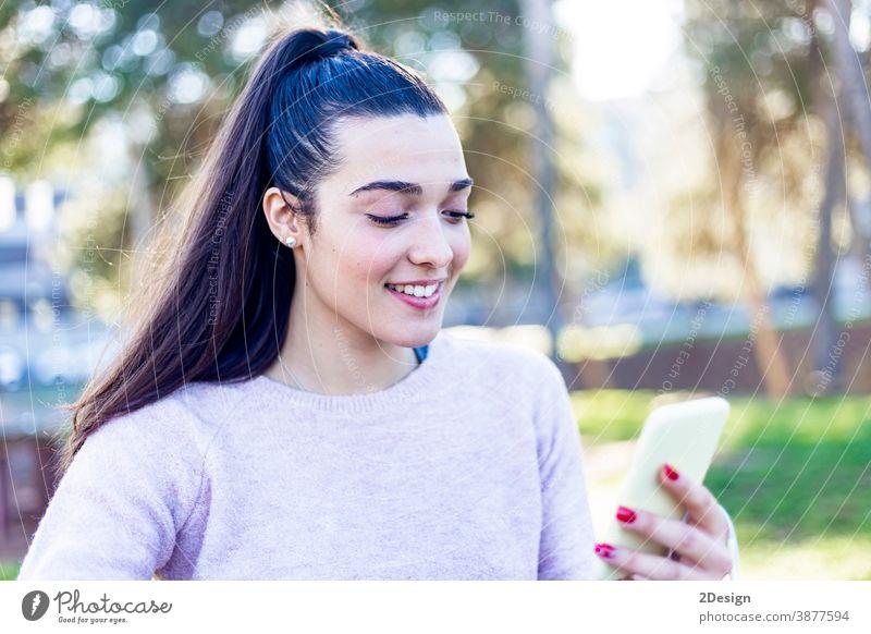 Junges, schönes, lächelndes Mädchen sitzt im Park und benutzt ihr Mobiltelefon jung Frau Telefon Sitzen Mobile Lächeln Technik & Technologie Smartphone