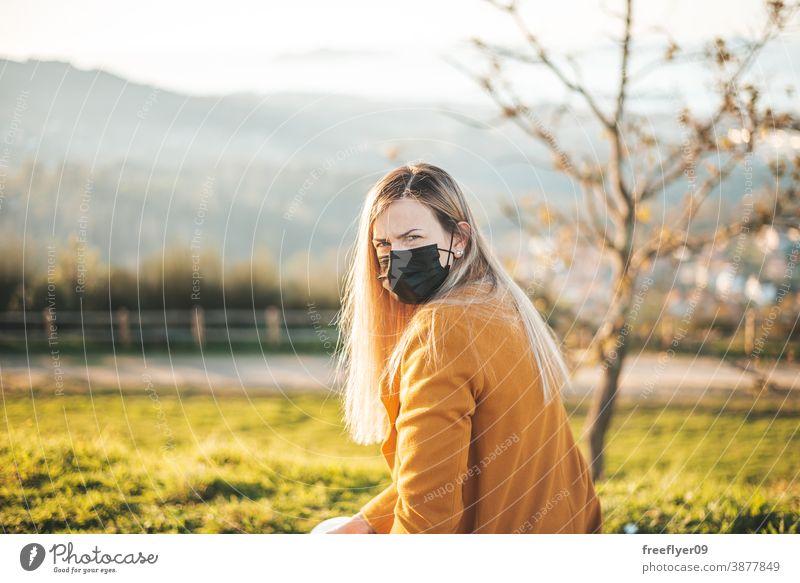 Frau im gelben Mantel auf einer Bank sitzend mit Gesichtsmaske Sitzen Coronavirus COVID Winter Herbst betrachtend Vigo Galicia Natur im Freien Freiheit