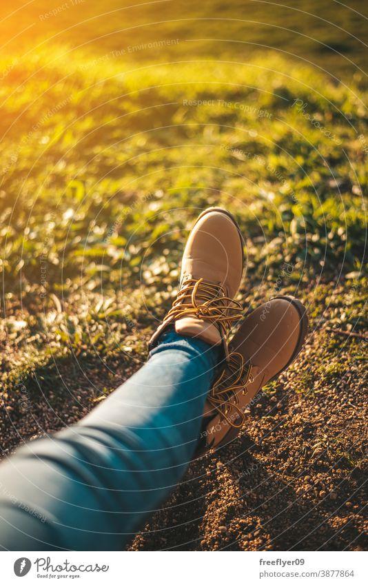Detail einiger Füße beim Entspannen Stiefel entspannend Frau Gras Textfreiraum Fuß Erholung Sonnenuntergang wandern Tourismus Tourist unkenntlich