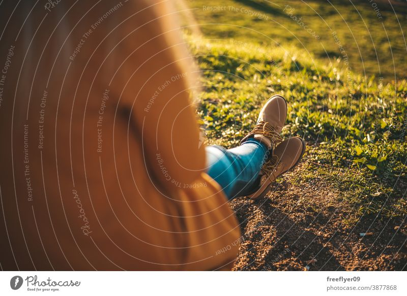 Frau entspannt sich bei Sonnenuntergang gelb Mantel Herbst Winter Textfreiraum unkenntlich Stiefel entspannend Gras Fuß Erholung wandern Tourismus Tourist