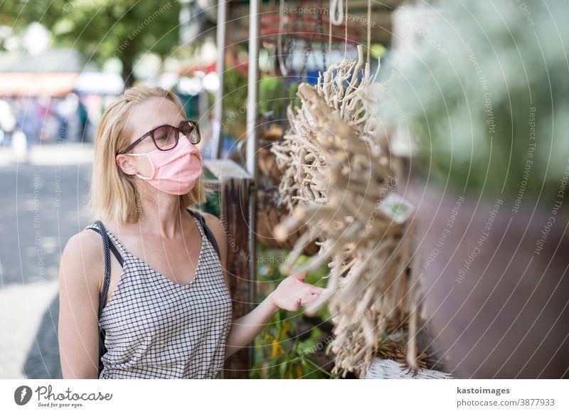 Lässige Frau beim Einkaufen im Freien an Marktständen mit Fasenmasken zum Schutz vor der Coronavirus-Pandemie in München, Deutschland Mundschutz Lifestyle