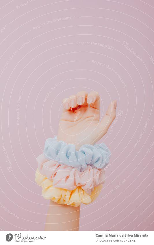 Hand mit bemalten Nägeln und Scrunchies auf dem Arm. Im Atelier gemachtes Foto mit rosa Hintergrund. Kunst Schönheit Nahaufnahme Mode Frau feminin festlich