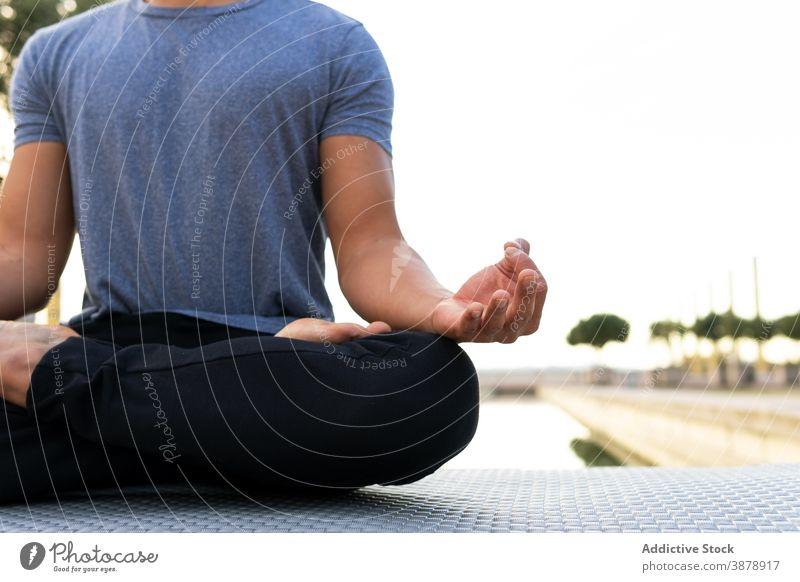 Gelassener Mann in Lotus-Pose im Park vermittelnd meditieren Yoga Harmonie Asana padmasana beweglich Beine gekreuzt üben männlich Unterlage sich[Akk] entspannen