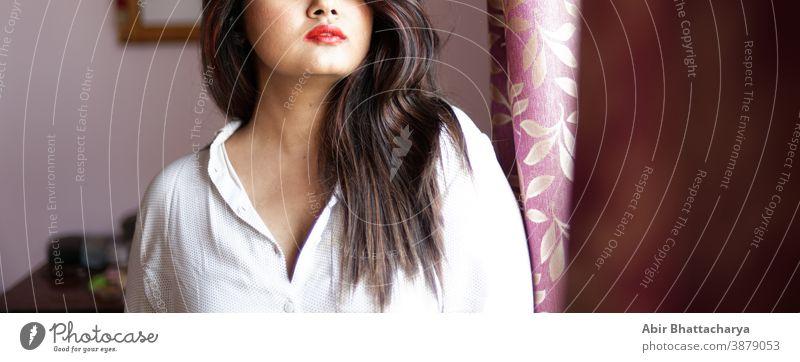 Halbgesichtporträt eines indisch-bengalischen brünetten, süßen Mädchens in sexy weißem Hemd, das vor einem Fenster steht. Indischer Lebensstil. Erwachsener