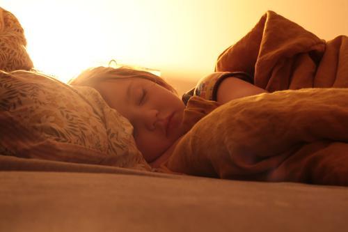 Kind schläft gemütlich im Bett schlafend Schlafenszeit Abendlicht Warme Farbe Augen geschlossen Augen zu träumen Bettdecke Kissen Federbett Nachtlicht