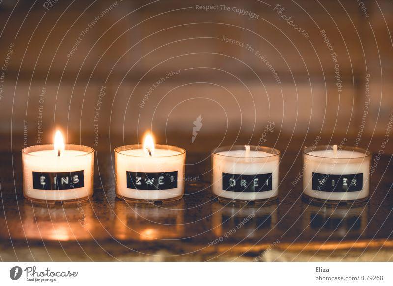 Zwei Kerzen brennen an einem minimalistischen Adventskranz, bestehend aus durchnummerierten Teelichtern zwei 2. Advent Zweiter Advent Weihnachtszeit vier