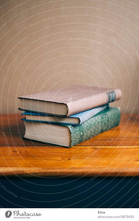 Drei Bücher liegen gestapelt auf einer Kommode aus Holz Bildung Literatur Buch Lesestoff alt Roman lesen Stapel Bücherstapel