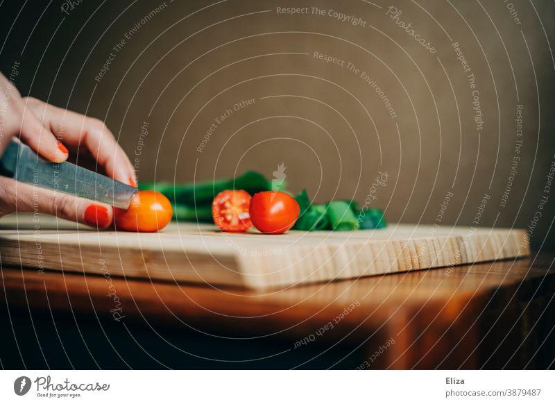 Frauenhände schneiden Tomaten auf einem Schneidebrett. Frühlingszwiebeln Zubereitung Essen kochen frisch Hände Küche Essen zubereiten Messer Lebensmittel