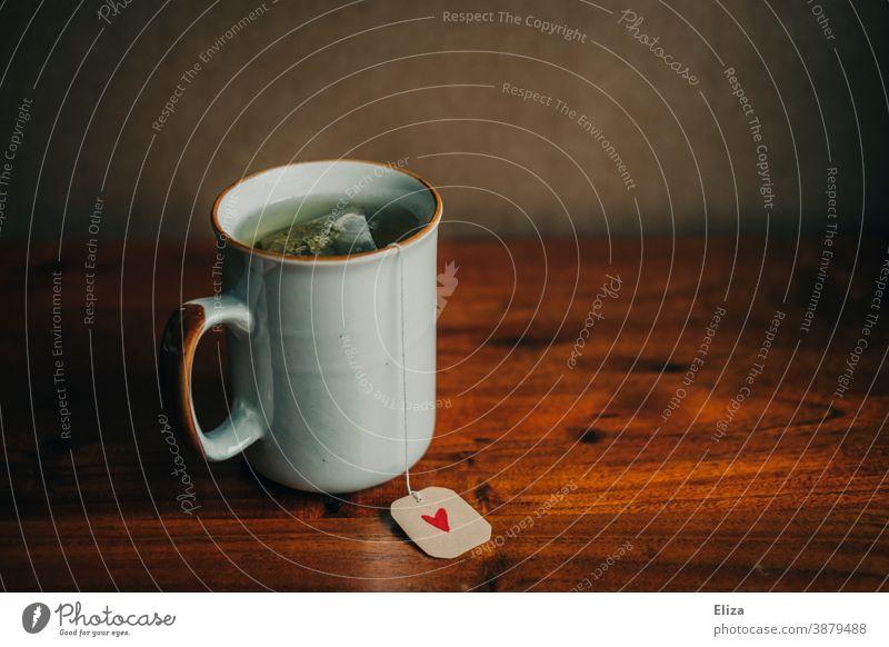 Eine Tasse mit Teebeutel und einem kleinen Herz auf dem Etikett. Tee trinken. Teetasse gemütlich Wärme Winterzeit gesund werden Wohlbefinden Becher Teetrinken