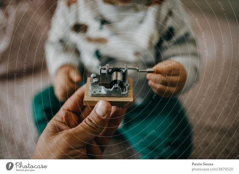 Nahaufnahme eines Kleinkindes, das eine hölzerne Spieluhr hält Spieldose Ton Musik Musiknoten Musikinstrument Kind musizieren Klang Holz Detailaufnahme