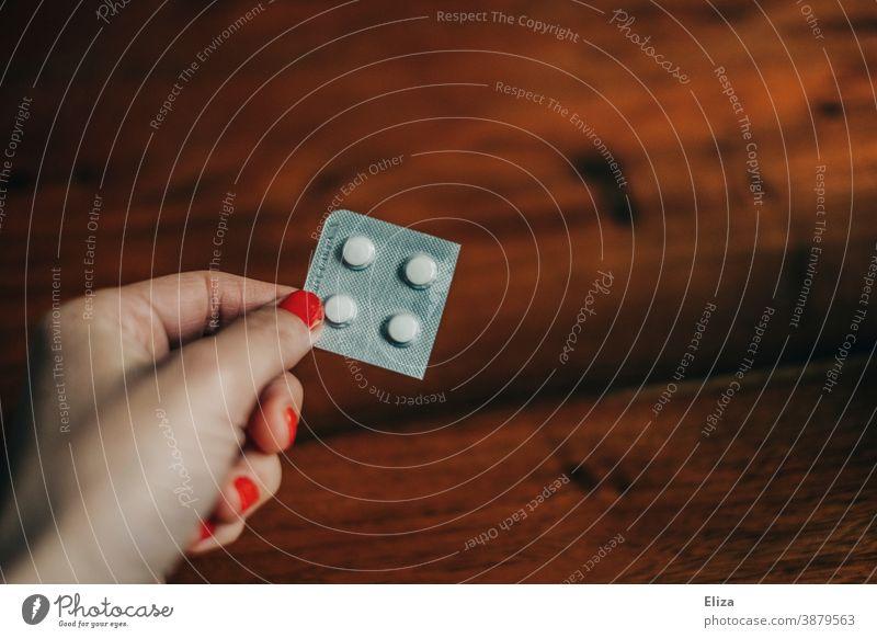 Eine Frau hält einen Medikamentenblister mit vier weißen Tabletten in der Hand Blister Durchdrückpackung Medikamentverpackung Tablettenverpackung Pillen Medizin