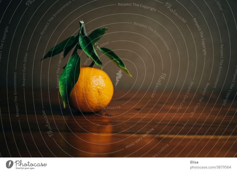 Eine Mandarine mit Zweig und Blättern auf Holz Zitrusfrüchte Clementine orange Blatt Mandarinen Vitamin Winter Vitamin C