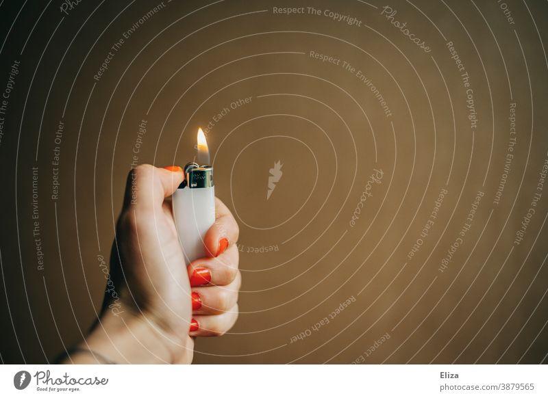 Eine weibliche Hand hält ein brennendes Feuerzeug anzünden zündend Licht Flamme heiß Nagellack entzünden zündeln Frauenhand Zünden Hintergrund neutral Wärme