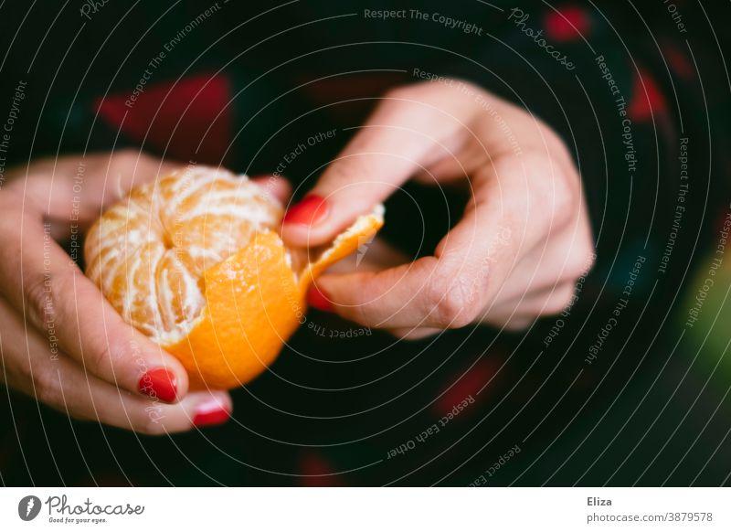 Hände einer Frau schälen eine Mandarine Nagellack Obst süß frisch lecker Vitamin V orange Clementine Zitrusfrucht roter Nagellack Frucht Winter saftig