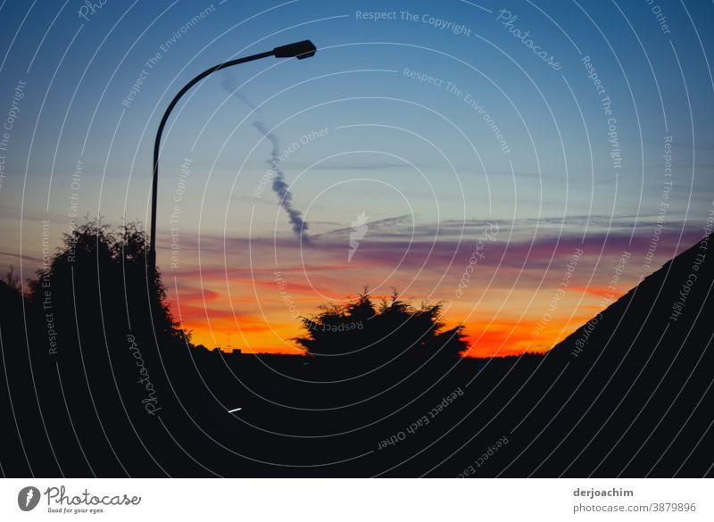 Sonnenuntergang wie in der Karibik . Die Laterne ist noch aus.Der Schatten der Bäume ist sehr markant im Gegenlicht . Eine letzte Spur von einer Rauchfahne  ist noch am Himmel  zu sehen.
