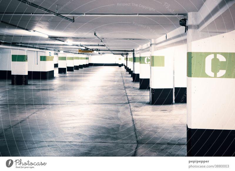 Tiefgarage mit farbiger Buchstabenkennung Garage Parkhaus Beton Parkplatz parken Parkdeck Wand Asphalt parkgarage Verkehrswege Menschenleer abwärts Gebäude kalt