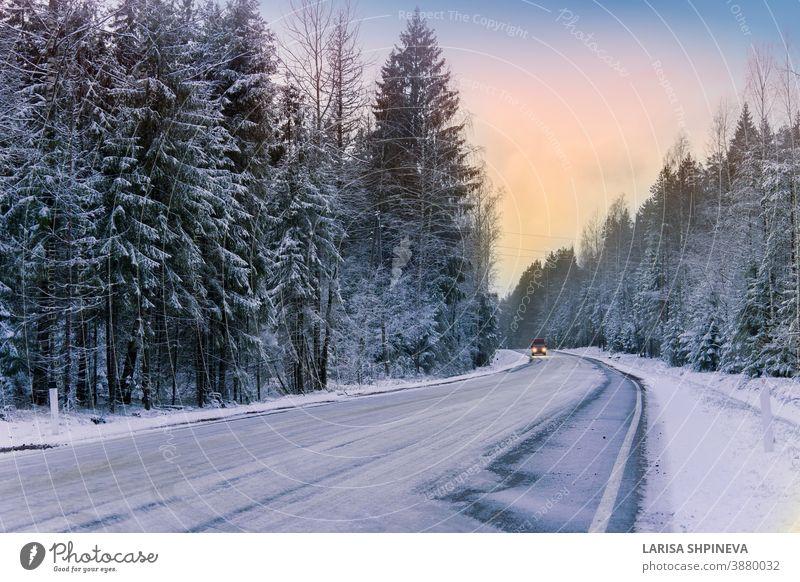 Auto fährt auf leerer, verschneiter Strasse im Winterwald. Wunderschöne frostig weisse Landschaft in der Morgendämmerung. Straße Saison Wald Eis Szene