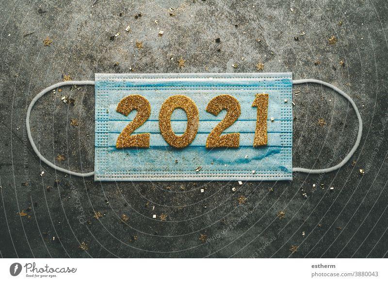 Hintergrund zum Konzept der Silvesterfeier.medizinische Maske mit den Zahlen 2021.Covid-19 Neujahrskonzept Weihnachten Chirurgische Schutzmaske Coronavirus