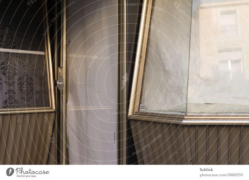 Teil einer Fassade eines alten geschlossenen Geschäfts aus den 60zigern mit Schaufenster und Tür aus goldfarbenem Aluminium und Hinweis protection electronique